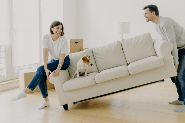 a woman and her dog sitting on the couch while a man tries to move it