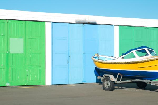A little boat on a trailer going into self storage unit