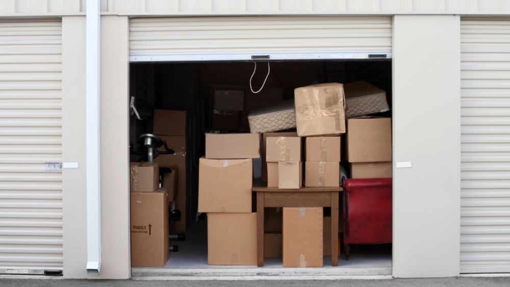 Open storage unit cluttered with boxes overflowing