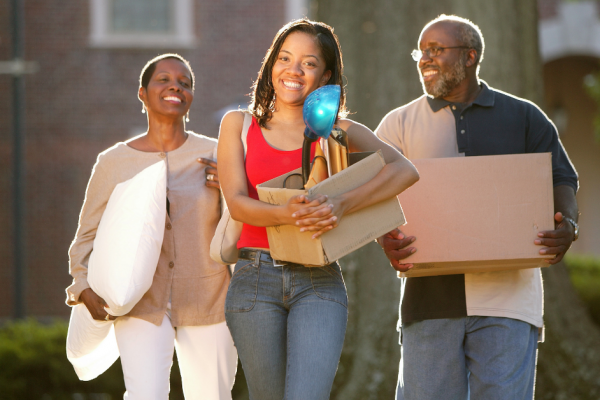 Female college student holding box and moving with parents