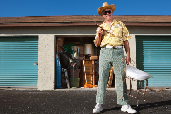 A well-dressed man in a straw hat, yellow floral shit, white plaid pants and a cigar in front of a storage unit.