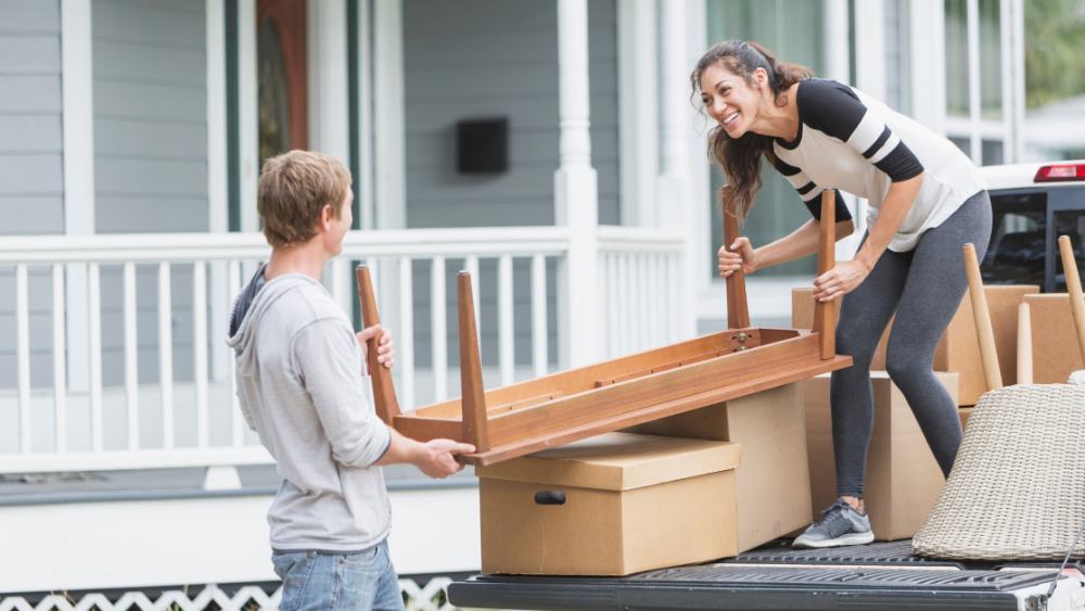 Young couple smiling and laughing while loading furniture onto a pickup truck