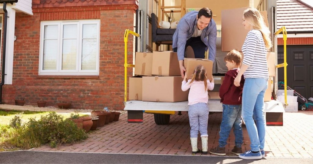 Family unloading boxes out of a u-Haul truck