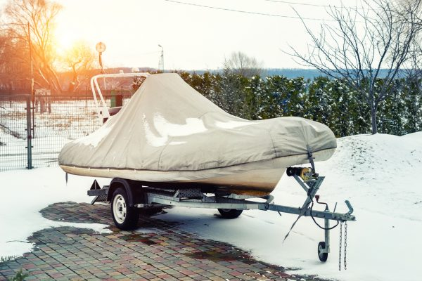 A small, covered boat on a trailer in the snow.