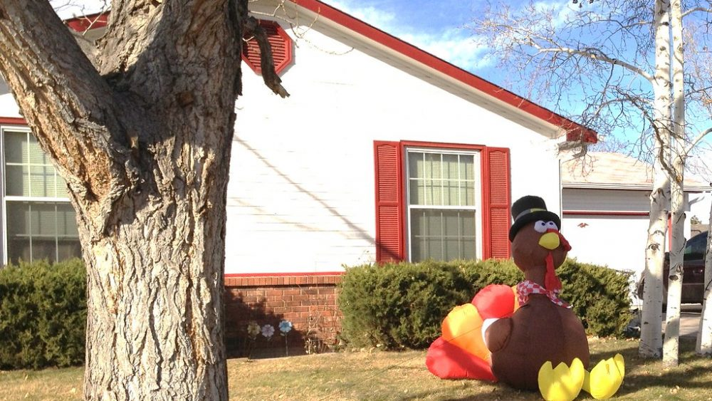 Image of a giant inflatable turkey wearing a hat on a lawn in front of a house.